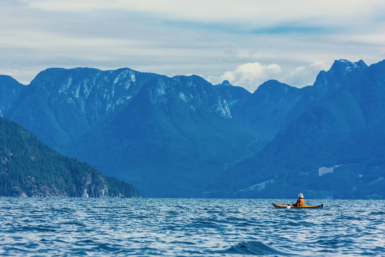 A kayaker sits and watches the Coast Mountains on one of our multi-day kayak tours british columbia