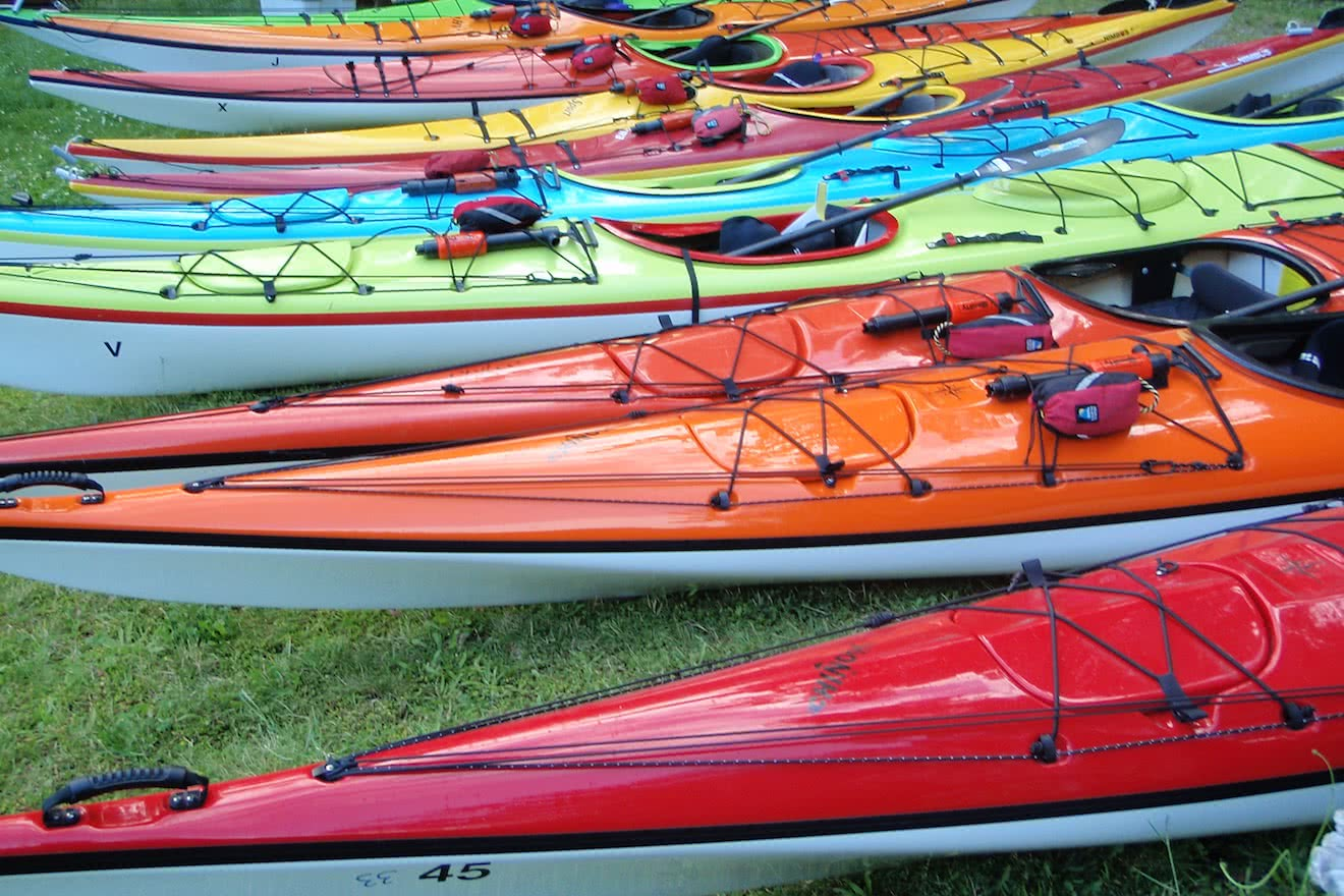 Colourful sea kayak rentals lined up in Okeover Inlet