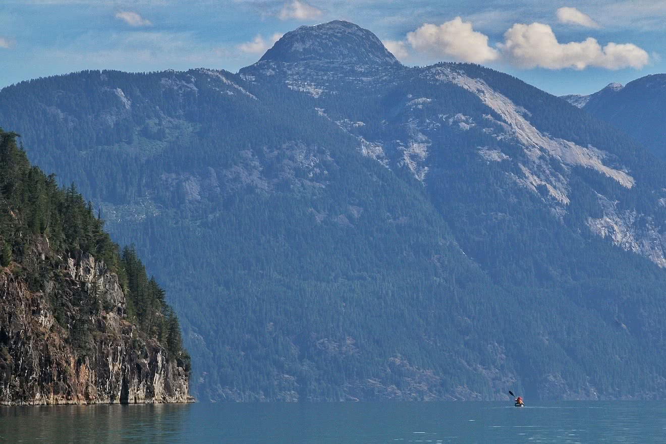 A kayaker appears tiny as she paddles into the awesome mountain scenery of Toba Inlet