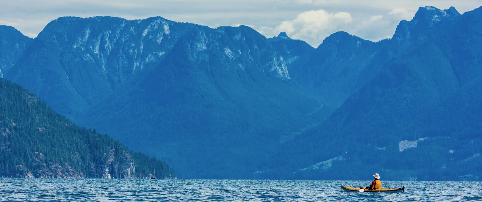 A kayaker sits and looks at the Coast Mountains on one of our multi-day kayak tours