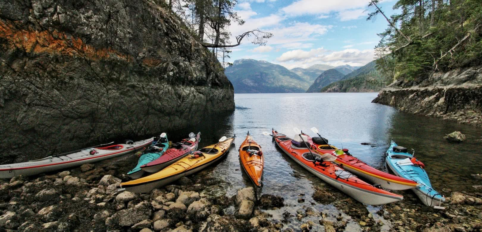 Kayaks at the tide line during a quick break on on of our sea kayak expeditions