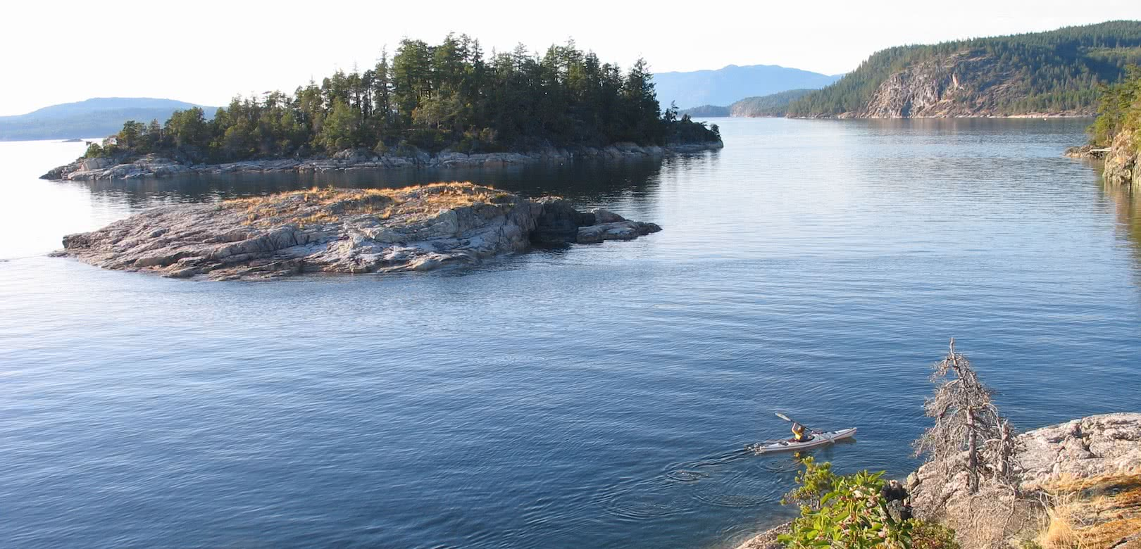 A young kayaker paddles along the shore on one of our Copeland Islands day tours