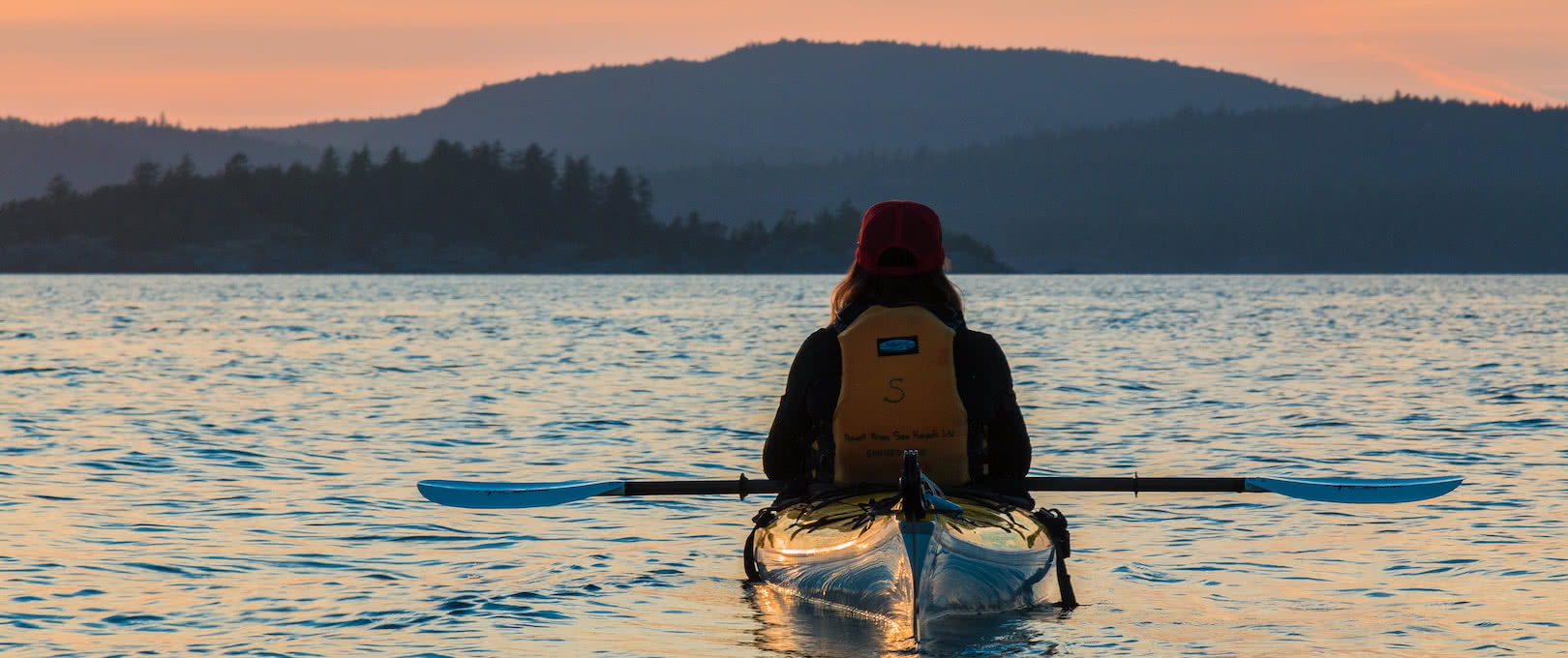 A guest watches the sunset from her kayak on a multi-day camping tour