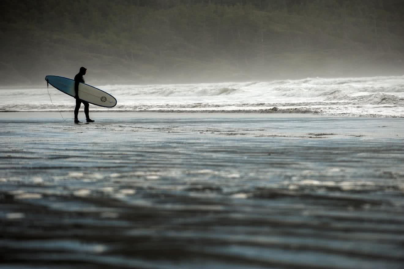 A surfer in a wetsuit in Tofino on Vancouver Island