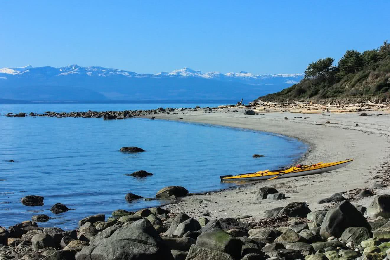 A kayak pulled up on the sandy beach at Duck Bay on Savary Island