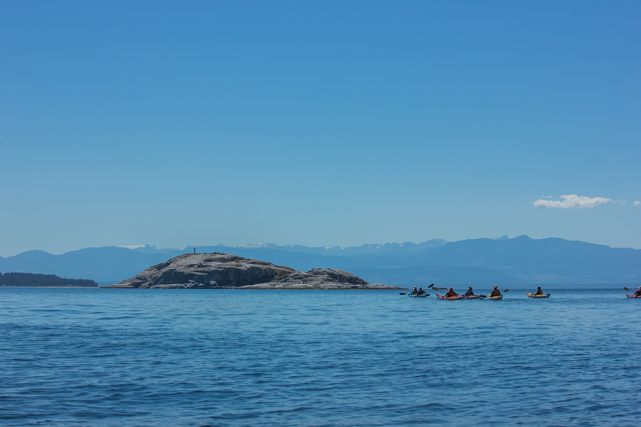 A group of sea kayakers paddling to Major Rock near the Copeland Islands