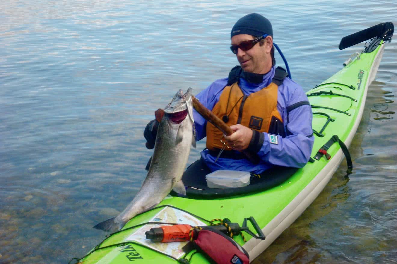 A guest after a successful catch of Salmon from a kayak in Desolation Sound