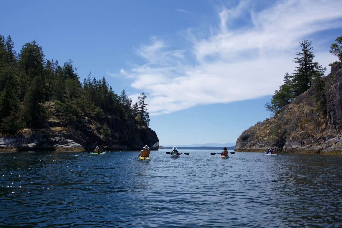 Paddling between two islets in the Copeland Islands on a sea kayak tour