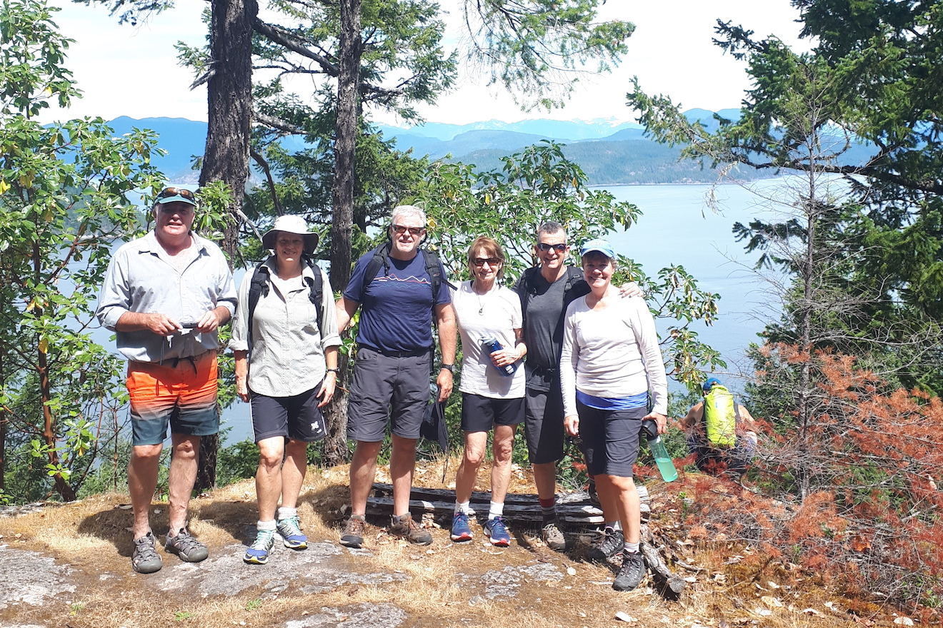 A group at Cabana Desolation Eco Resort standing at the viewpoint of a hike in Desolation Sound