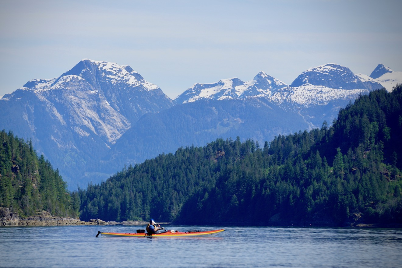 The Coast Mountains are seen by a solo paddler kayaking in Waddington Channel