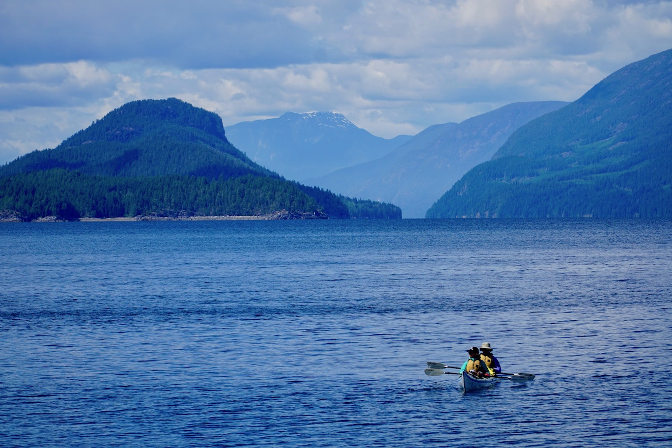 Two kayakers in a double kayak sit still in the middle of Desolation Sound, with Lewis Channel behind them