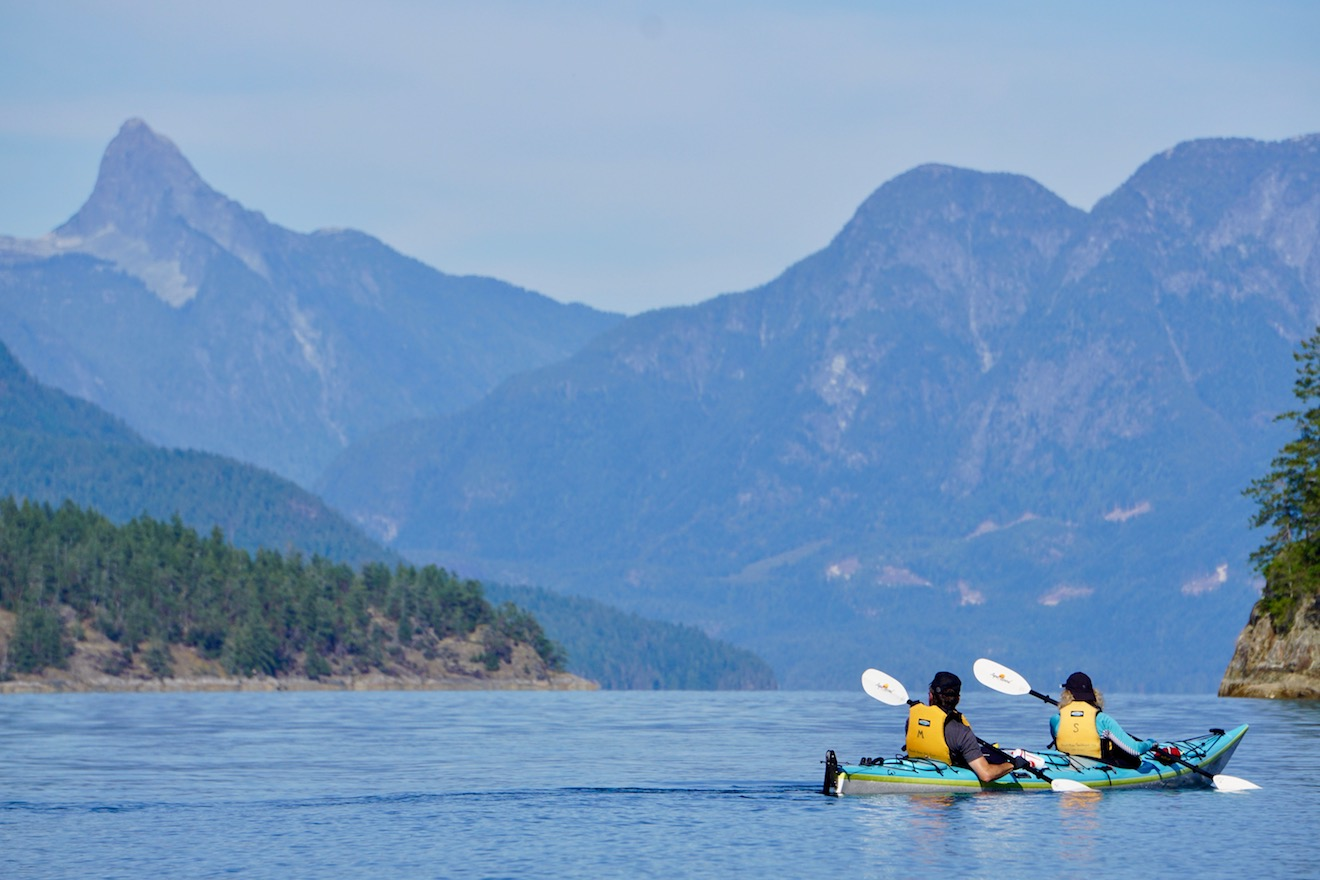 Two paddlers in a double kayak paddling in Desolation Sound and appreciating Mount Denman