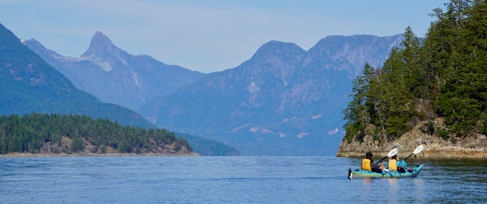 Paddlers in a double kayak paddle in Desolation Sound with Mount Denman in the background
