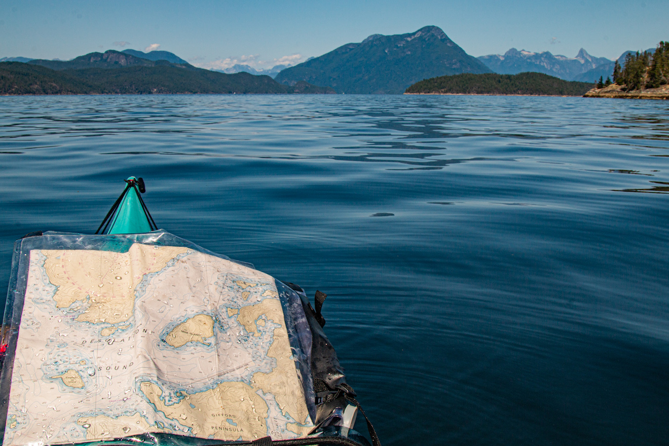 A kayak with a chart of Desolation Sound, and Mount Denman and the Coast Mountains in the background