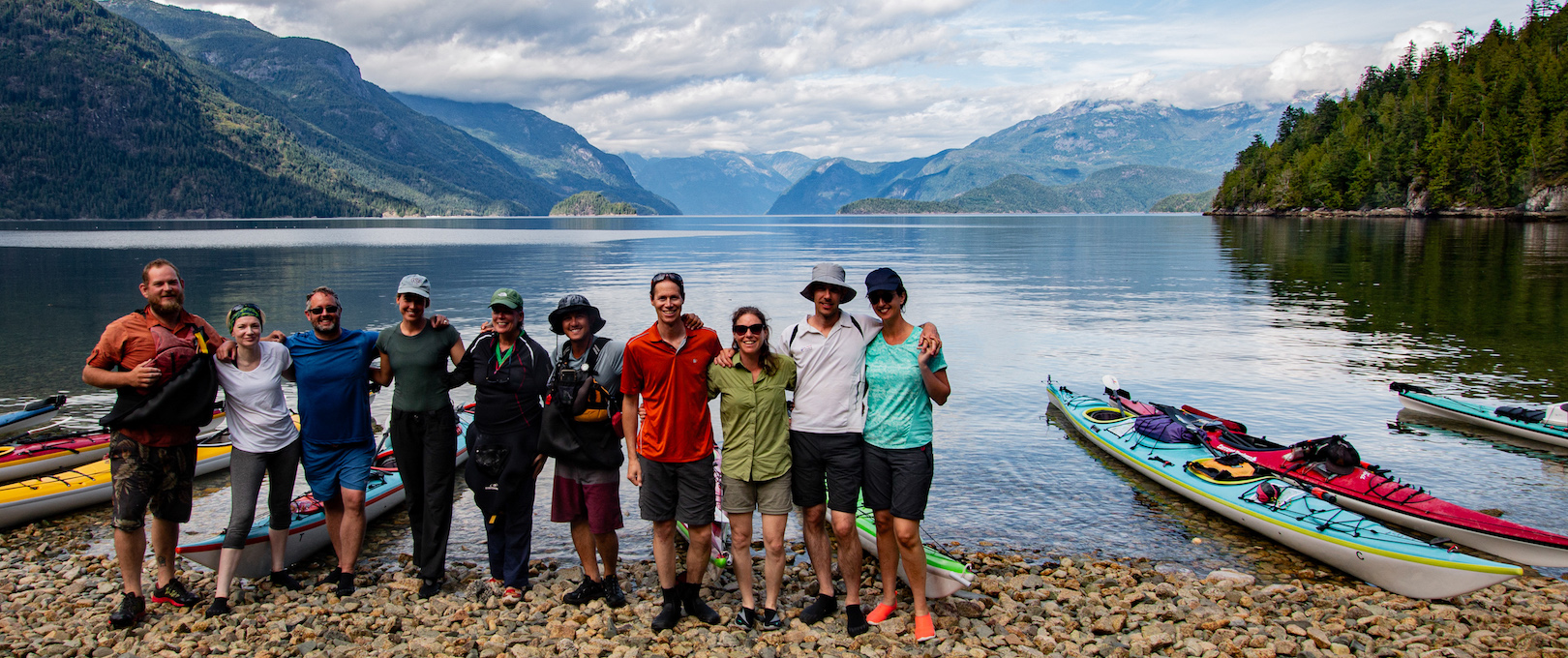 A tour group posing with guides at the mouth of Toba Inlet on one of our sea kayak expeditions