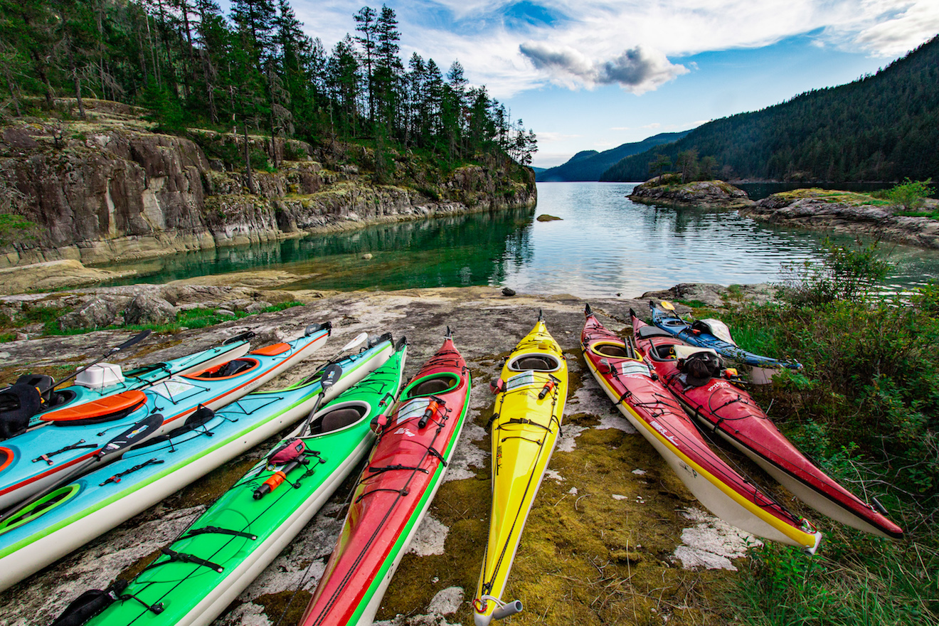 9 kayaks stored about the high tide line in Walsh Cove in northern Waddington Channel