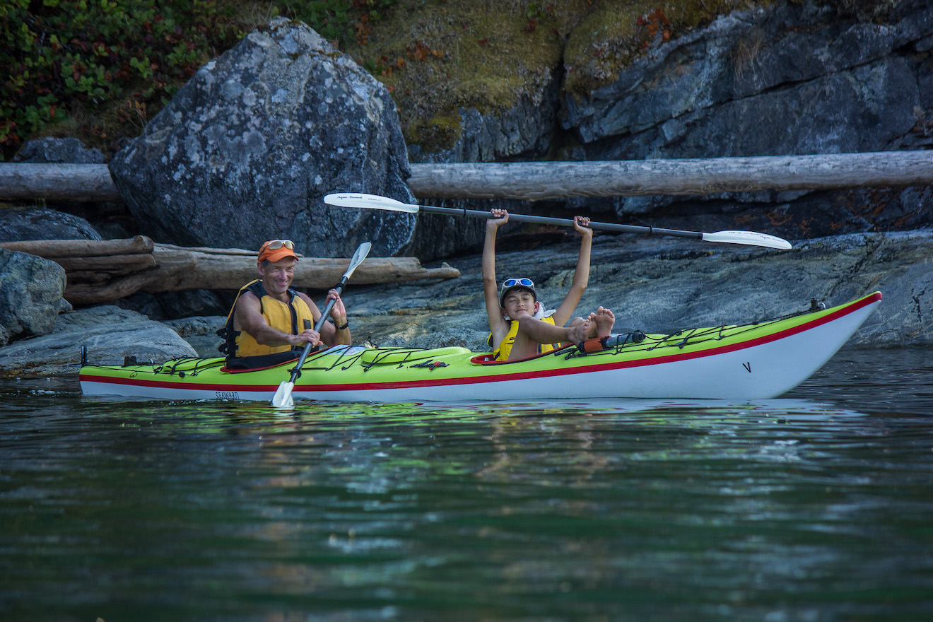 Father and son kayaking in Desolation Sound on a family kayaking trip